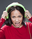 Screaming teenager rocking out holding earphones Royalty Free Stock Photo