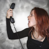 Screaming into telephone. Royalty Free Stock Image