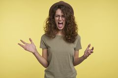 Screaming upset brunette young woman,got in anger with her boyfriend, over yellow background stock images