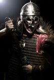 Screaming viking warrior with sword, armour and helmet over blac Stock Photos
