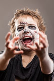 Screaming walking dead zombie child boy. Halloween or horror concept - screaming walking dead zombie child boy reaching hand Royalty Free Stock Photography