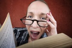 Screaming woman with big eyes reading a book Royalty Free Stock Images
