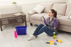 Screaming woman cleaning floor with lots of tools. Young tired girl surprised of detergents quantity, copy space Royalty Free Stock Photography