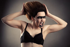 Screaming woman with dark makeup and lush hair in bra Royalty Free Stock Photos