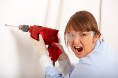 Screaming woman drilling hole. Beautiful screaming woman working drilling hole in white wall in home, wearing protective  gloves and glasses, ladder in Royalty Free Stock Image