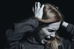 Screaming woman with hallucinations. And psychosis against black background Royalty Free Stock Image