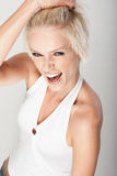 Screaming woman having a temper tantrum. High angle view of an emotional beautiful young woman screaming and having a temper tantrum grabbing her hair in her Royalty Free Stock Photos