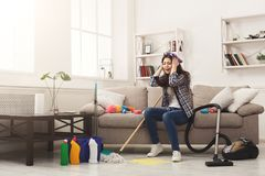 Screaming woman with lots of tools. Screaming woman with lots of cleaning tools. Young tired girl surprised of detergents quantity and mess in house, copy space Stock Photo