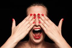 Screaming woman. With red nails covering her face Stock Image