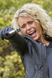 Screaming woman shooting from handgun Stock Photography