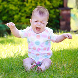 A screaming and wriggling baby in a colorful vest on the grass Stock Photos