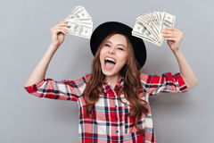 Screaming young brunette lady holding money. Royalty Free Stock Images
