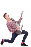 Screaming young guitarist playing his guitar. Rock star with a guitar screaming isolated over white background . rock and roll image of a young man playing an Stock Photography