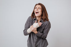 Screaming young lady with the plaster on hand. Image of sick screaming young lady with the plaster on hand dressed in shirt standing  over gray background Royalty Free Stock Photos