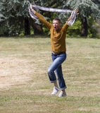 Screaming young man running with scarf in hands for celebration. Celebrating success outdoors concept - crazy middle age man running wild in a park for personal Royalty Free Stock Images