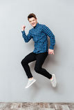 Screaming young man standing over grey wall and jumping. Picture of screaming young man standing over grey wall and jumping. Looking at camera stock photography