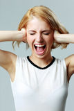 Screaming young woman with closed ears Royalty Free Stock Photography