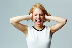 Screaming young woman with closed ears Royalty Free Stock Photos