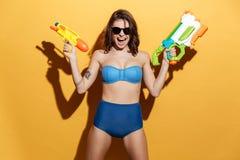Screaming young woman in swimwear holding toys water gun Stock Image