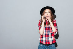 Screaming young woman talking by phone. Image of screaming shocked young woman standing over grey wall wearing hat talking by phone. Looking at camera Royalty Free Stock Photos
