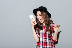 Screaming young woman talking by phone. Picture of screaming young woman standing over grey wall wearing hat talking by phone. Looking aside Royalty Free Stock Photography