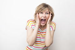 Screaming young woman on white. Screaming young woman in colorful t-shirt on white Stock Photo
