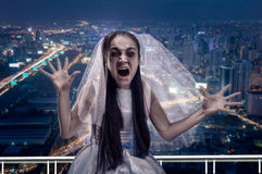 Screaming zombie bride, night city on background Royalty Free Stock Photo