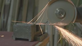 Screeching disk of the angle grinder sinked into the metal. A ray of sparks splashed light upon a young face behind the protective goggles stock video footage