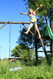 Screeming girl jumping from a slide. Screeming and shouting little girl - barefoot kid jumping from a slide and flying Royalty Free Stock Photography