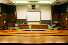 Screen in lecture hall. A wood panelled university lecture theatre/conference hall Royalty Free Stock Image