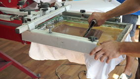 Screen printing manufacturing on t-shirts. Worker print an image on fabric on a hand bench. Image creating process stock footage