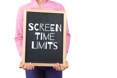 Screen time limits for children issue. Screen time limits for children issue depicted with child holding blackboard with text and copy space stock photo