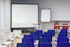 Screen for video projector is in business room. Hall is ready for conference Royalty Free Stock Photography