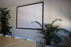 Screen for video projector in the meeting room. White royalty free stock photo