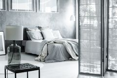 Screened bedroom with glass lamp. Glass lamp on black table in screened bedroom with grey bedding on king-size bed against concrete wall Stock Photos