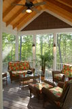 Screened in Porch Deck. Screened in porch with floral furniture, beamed ceilings, wall sconces Stock Images