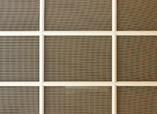 Screened Window. Brown window screen with white wooden dividers Stock Images