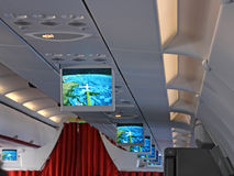 Screens in an Airplane. The ceiling with the information LCD screens showing the current position and direction of an airplane over the Greek islands (focus is Royalty Free Stock Photography
