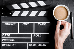 Screenwriter desktop with movie clapper board dark background to Stock Image