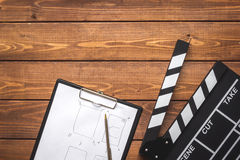 Screenwriter desktop with movie clapper board wooden background top view Royalty Free Stock Photos