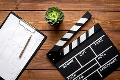Screenwriter desktop with movie clapper board wooden background top view. Screenwriter desktop with movie clapper board on wooden background top view Royalty Free Stock Image