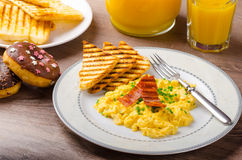 Scrembled eggs with panini toast and donut Stock Images