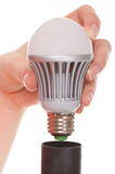 Screw bulb into a cap Stock Photography