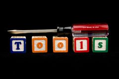 Screw driver on blocks spelling tools Stock Photography