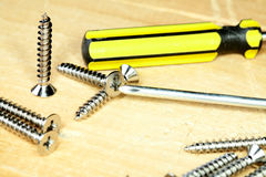 Screw-driver screws on a  board Stock Image