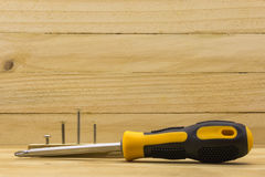 Screw driver. Set head screw driver and screw on wood background Stock Photography