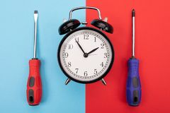 Screw-drivers and black metal alarm clock on background. Colorful plastic screw-drivers and black old-fashioned alarm clock on blue-red background stock photography