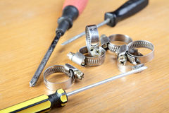 Screw-drivers and clips for hoses on a table. Screw-drivers and clips for hoses on a wooden table stock photos