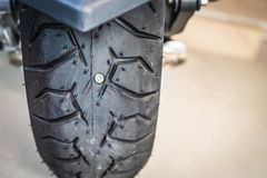 nail or Iron stuck puncturing motorcycle or big scooter tire at a motorcycle repair shop. Selective focus.motorcycle repair royalty free stock photos