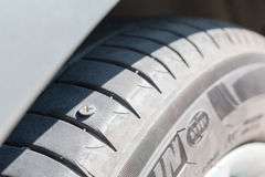 nail puncturing tire. Stock Image